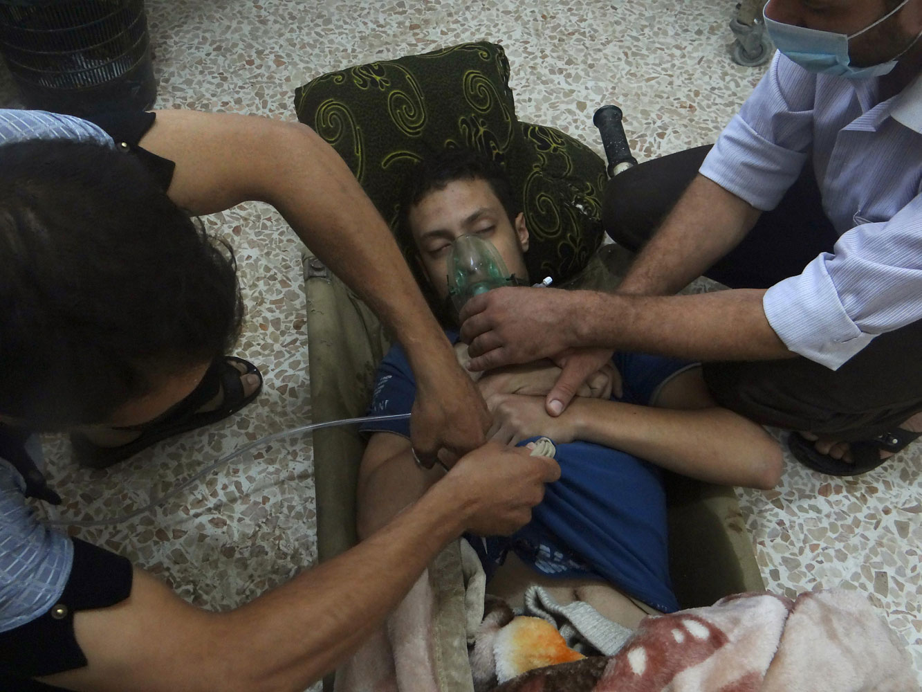 A man, affected by what activists say is nerve gas, breathes through an oxygen mask in the Damascus suburbs of Jesreen, August 21, 2013.
