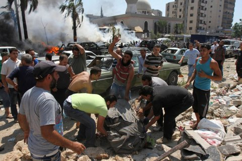 Men remove a dead body from the scene of an explosion outside one of two mosques in Lebanon's northern city of Tripoli, on Aug. 23, 2013.