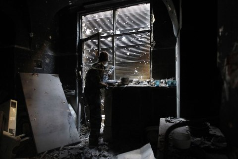 A Free Syrian Army fighter looks outside while holding his weapon as he takes cover inside a damaged shop in the old city of Aleppo