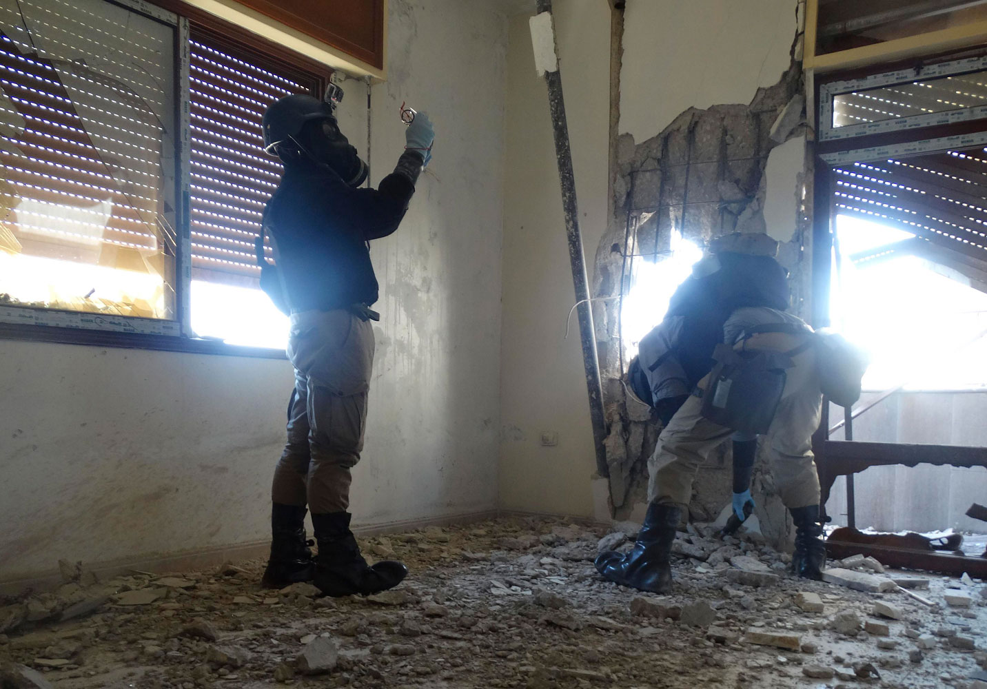 U.N. chemical weapons experts, wearing gas masks, inspect one of the sites of an alleged chemical weapons attack in the Damascus' suburb of Zamalka, August 29.