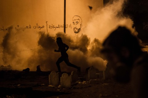 Protesters run from the toxic gas shot by riot police in Bahrain, on Aug. 5, 2013.