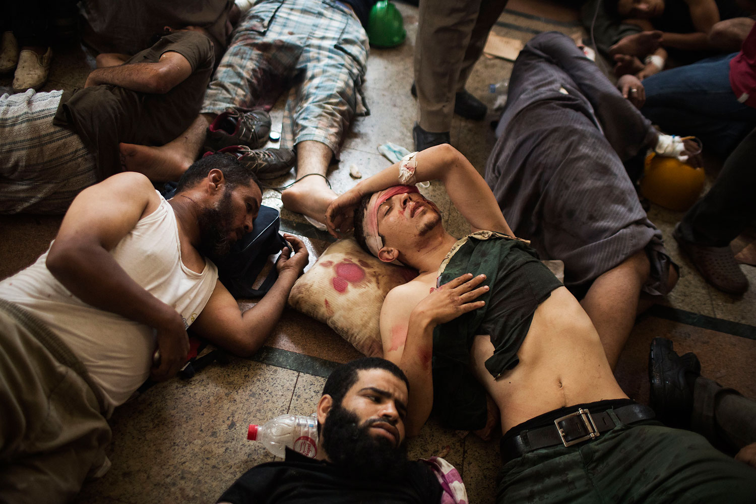 Wounded supporters of ousted Islamist President Mohammed Morsi lie on the floor of a makeshift hospital at a sit-in at Cairo's Nasr City district, Egypt, Aug. 14, 2013.