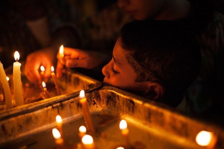 An Egyptian Coptic Christian child lights a candle in honor of the Virgin Mary at Al-Mahraq monastery in Assiut, Upper Egypt, Aug. 6, 2013.