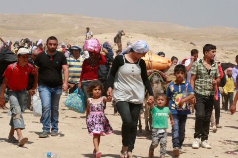 Syrian refugees cross into Iraq at the Peshkhabour border point in Dahuk, Iraq, on Aug. 20, 2013.