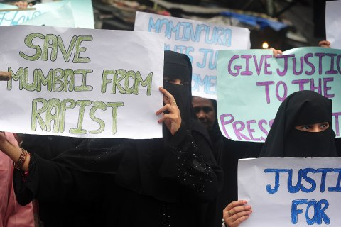 Indian Muslim women hold posters during a protest march