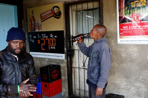 Men drink beer at a bar in Soweto, southwest of Johannesburg, on Aug. 8, 2012.