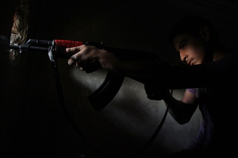 A Free Syrian Army fighter takes up a shooting position at the Seif El Dawla front in Aleppo, Syria, Aug. 4, 2013.