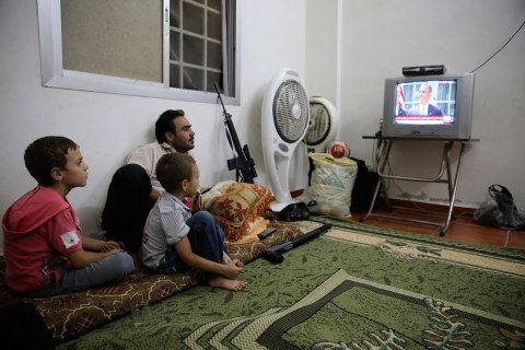 A Free Syrian Army fighter watches U.S. President Barack Obama's speech with his family in Ghouta, Damascus Aug. 31, 2013.
