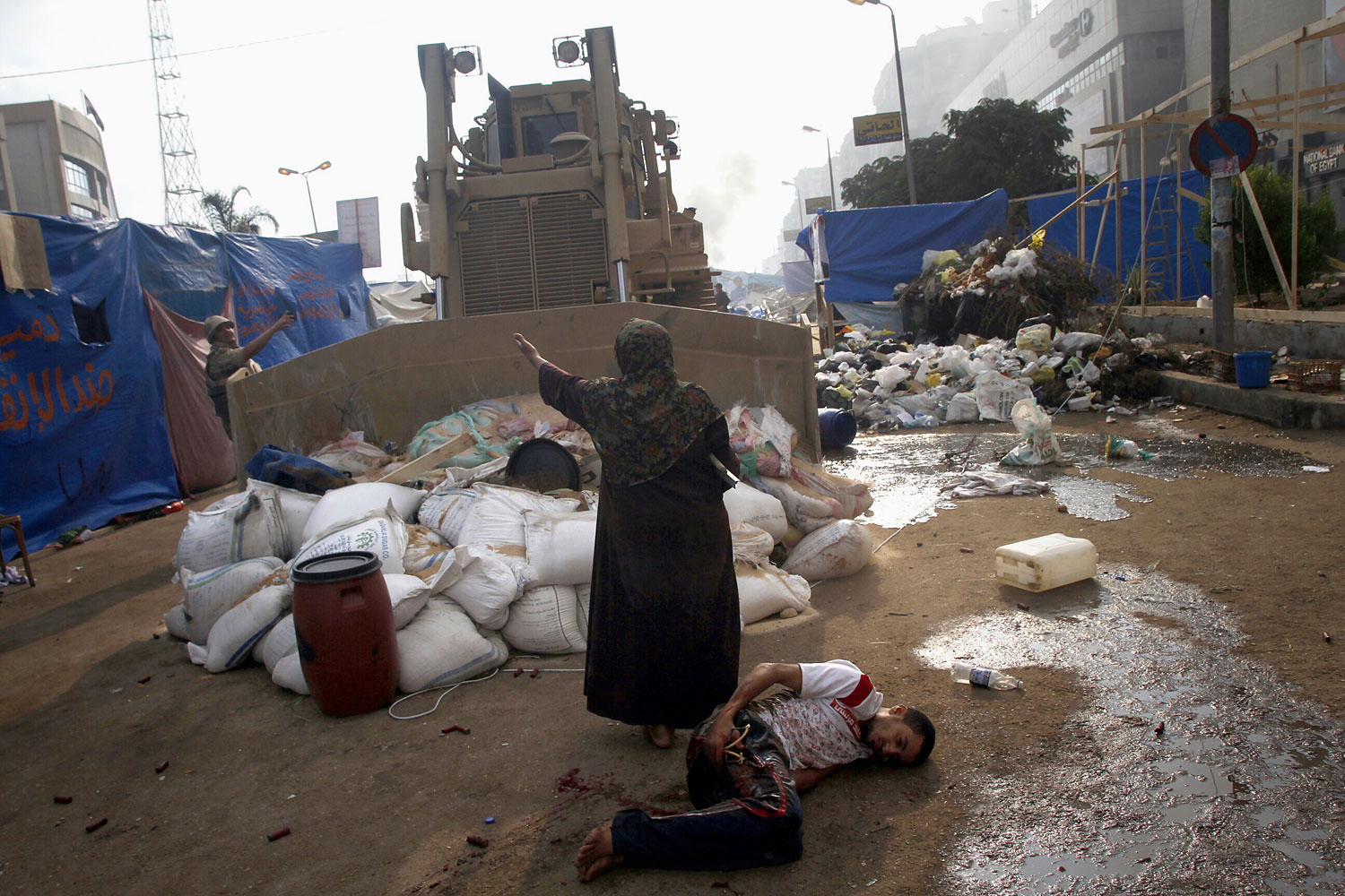 An Egyptian woman tries to stop a military bulldozer from hurting a wounded youth during clashes that broke out as Egyptian security forces moved in to disperse supporters of Egypt's deposed president Mohamed Morsi in a huge protest camp near Rabaa al-Adawiya mosque in eastern Cairo on Aug. 14, 2013.