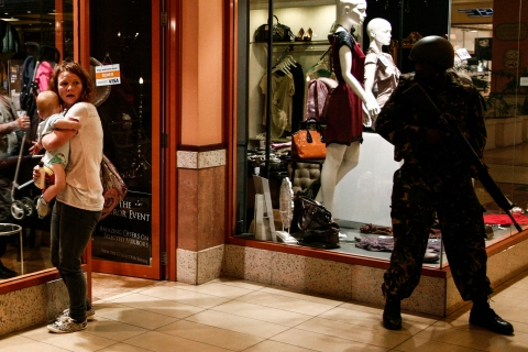 A woman shields a baby as a soldier stands guard inside the Westgate shopping mall after a shootout in Nairobi, Kenya, Sept. 21, 2013.