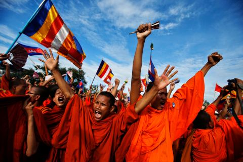 Buddhist monks who are supporters of the CNRP react as party leader Sam Rainsy announces the result of a meeting with Cambodian PM Hun Sen in Phnom Penh