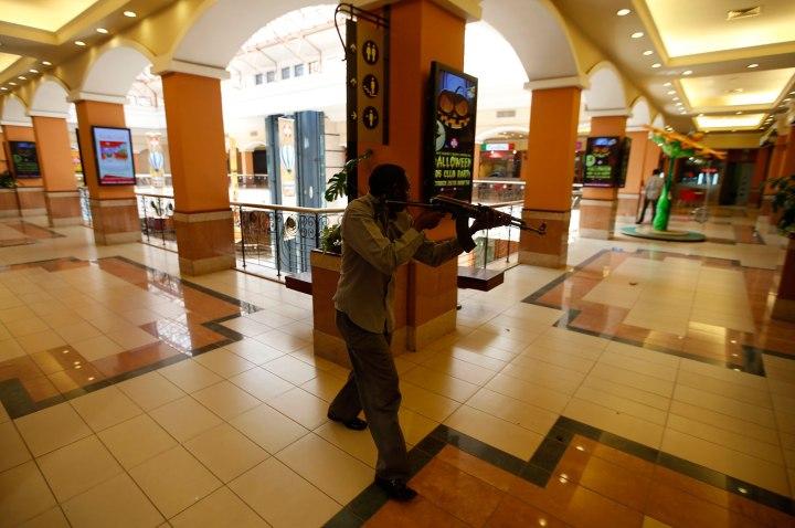 An armed police searches through a shopping centre for gunmen in Nairobi, Sept. 21, 2013.