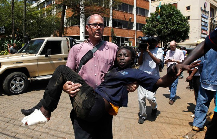 A journalist rescues a woman injured in a shootout between armed men and the police at the Westgate shopping mall in Nairobi Sept. 21, 2013.