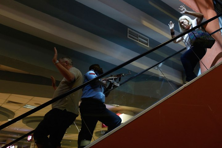 A police officer secures an area as civilians flee inside Westgate Shopping Centre in Nairobi Sept. 21, 2013.