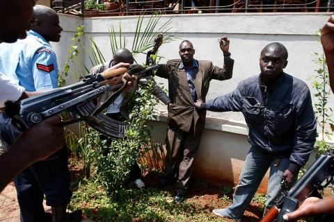Policemen search a man for weapons as he walked out of Westgate Shopping Centre in Nairobi Sept. 21, 2013.