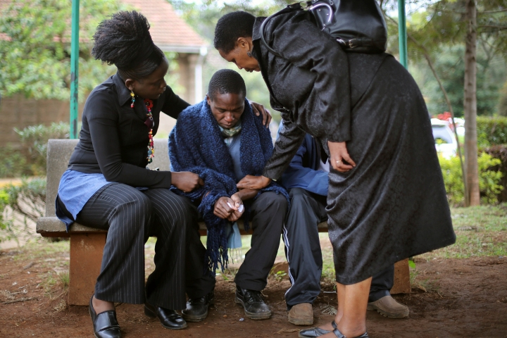 Stephen, center, who lost his father in Saturday's attack at the Westgate Mall  in Nairobi, Kenya, is comforted by relatives as he waits for the post mortem exam at the city morgue Monday, Sept. 23, 2013.