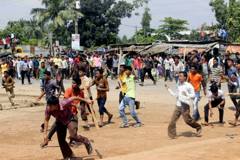 Garment workers throw pieces of bricks as they block a street during a protest in Gazipur.