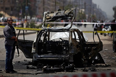 Egyptian security personnel gather at the scene of a bomb attack targeting the convoy of Egypt's Interior Minister Mohammed Ibrahim, in Nasr City, Cairo, Sept. 5, 2013.