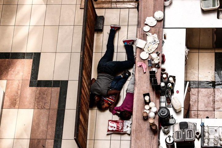 People take cover behind a counter at the Westgate shopping mall after a shootout in Nairobi, Kenya, 21 Sept. 2013.