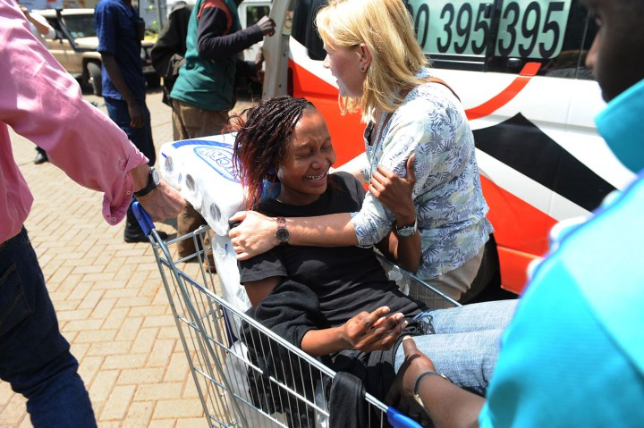 A woman is trolled into an ambulance after masked gunmen stormed an upmarket mall and sprayed gunfire on shoppers and staff on Sept. 21, 2013 in Nairobi.
