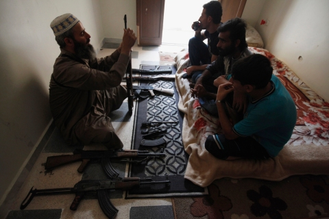 A Free Syrian Army leader teaches fellow members how to handle weapons in Aleppo