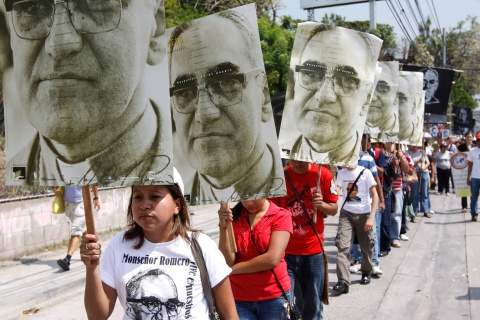 People carry photographs of late Archbishop Oscar Arnulfo Romero during the 31st anniversary of his assassination in San Salvador