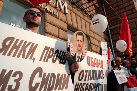 Participants hold placards and an image of Syrian President al-Assad during an anti-war protest organised by the Communist party near the U.S. embassy in Moscow