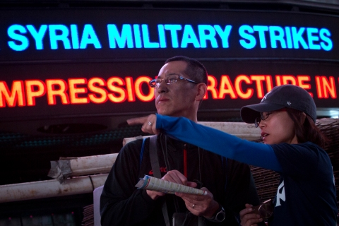 A news ticker refers to the situation in Syria as a couple look at a map in Times Square New York