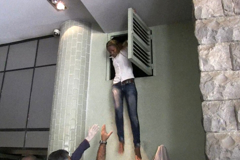 A Kenyan woman comes out of an air vent where she was hiding during an attack by masked gunmen at a shopping mall in Nairobi on Sept. 21, 2013.