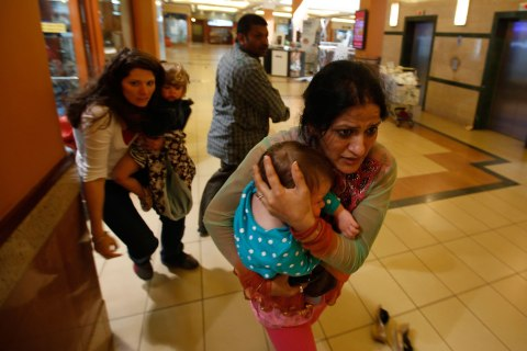 Women carrying children run for safety as armed police hunt gunmen who went on a shooting spree in Westgate shopping centre in Nairobi Sept. 21, 2013.