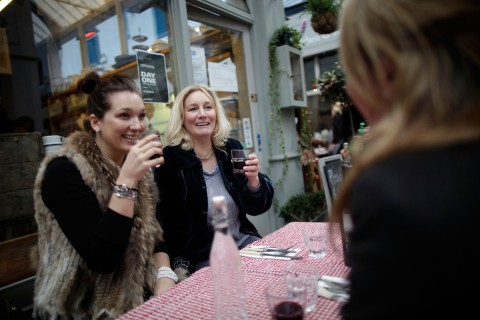 Two women drink wine at the Brixton Cornercopia kitchen and larder in the Granville Arcade in Brixton Village, England, on Jan. 28, 2012