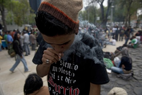 "A man smokes marijuana during the ""Marijuana Festival"" for its legalization at Luis Pasteur square, in front of building of the Mexican Senate in Mexico City, on Jan. 20, 2013."
