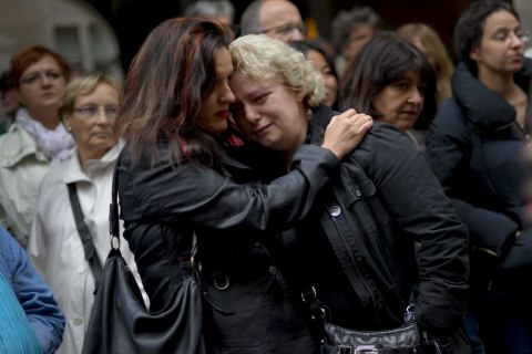 Women pay their respects at a memorial to killed Swiss sociotherapist Adeline Morel in Geneva, Sept. 16, 2013.