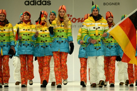 From right: German freeskier Benedikt Mayr and speed skater Monique Angermueller hold the German flag as they present the official German Olympic team's outfit for the 2014 Olympic winter games, in Duesseldorf, on Oct. 1, 2013.