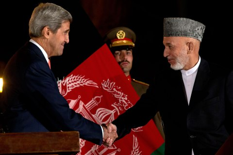 US Secretary of State John Kerry, left, shakes hands with Afghan President Hamid Karzai after a press conference at the Presidential Palace during an unannounced stop in Kabul on October 12, 2013.
