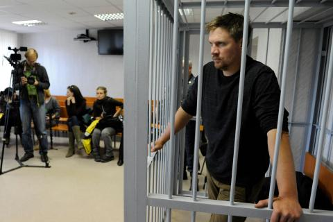 Greenpeace activist Anthony Perrett from Britain looks out from a defendants' box at a district court in Murmansk, Russia, on Sept. 29, 2013.