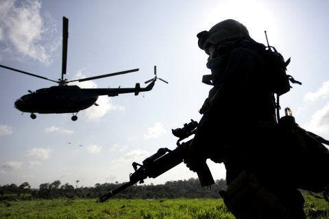 An anti-narcotics police officer stands guard as a helicopter secures the area at the Sierra Macarena National Park, Colombia, on Jan.19, 2006.