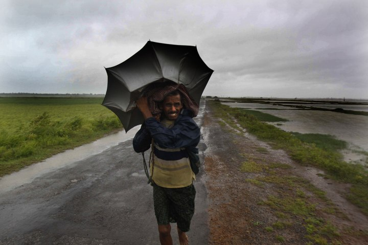 An Indian villager braving strong winds and rain reach for a safer place, in village Podampeta, in Ganjam district, India, Oct. 12, 2013.