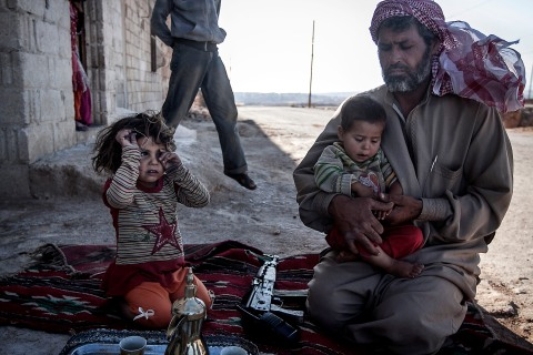 A Free Syrian Army fighter holds his son