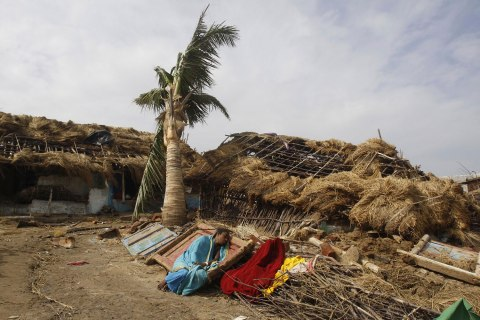 An Indian woman rests near her damaged house after returning to the cyclone hit Podampeta village on the Bay of Bengal coast in Ganjam district, Orissa state, India, Oct. 13, 2013.