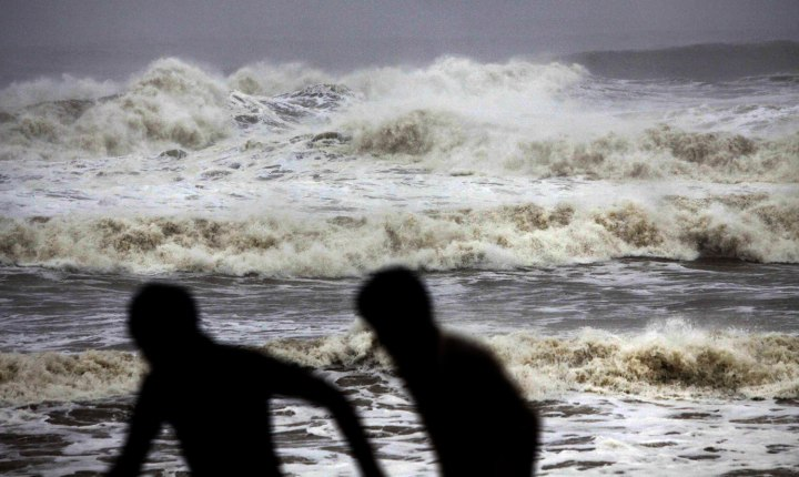 People run for shelter following a cyclone warning at the Bay of Bengal coast in Gopalpur beach in Ganjam district, India,  Oct. 12, 2013.