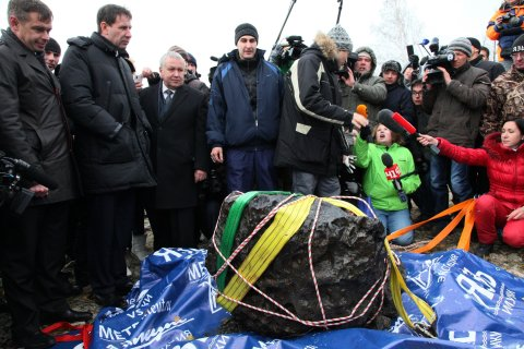 People look at what scientists believe to be a chunk of the Chelyabinsk meteor, recovered from Chebarkul Lake near Chelyabinsk, about 1500 kilometers (930 miles) east of Moscow, on Oct. 16, 2013.
