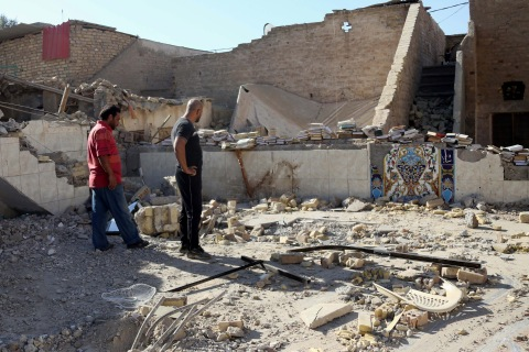 People inspect the ruins of the al-Hussein Shiite mosque a day after a suicide bomber struck in Musayyib, south of Baghdad, Sept. 30, 2013.