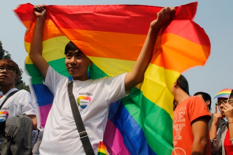 A participant holds up a rainbow flag during a LGBT event on a street in Hanoi