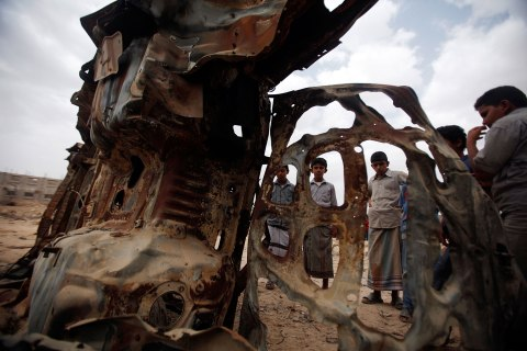 Boys gather near the wreckage of car destroyed last year by a U.S. drone air strike targeting suspected al Qaeda militants in Azan
