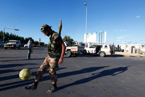 A rebel fighter loyal to Libya's interim government kicks a football as a battle rages nearby in Sirte