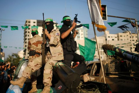 Palestinian Hamas militants take part in a military parade marking the first anniversary of the eight-day conflict with Israel in Gaza