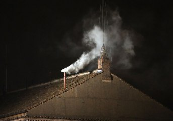 White smoke emits from the chimney on the Sistine Chapel as a new Pope is elected on March 13, 2013 in Vatican City, Vatican.