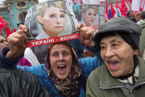 A supporter of jailed former Ukrainian Prime Minister Tymoshenko holds a portrait of her during a rally in front of the Parliament building in Kiev