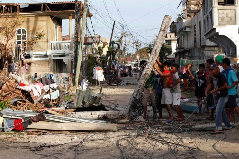 Residents clear the road of a fallen electric post after Typhoon Haiyan hit Daanbantayan town